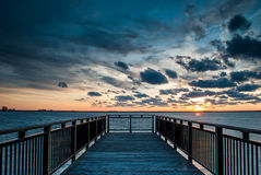 Harbor Boardwalk at Sunset. Photograph of a harbor boardwalk looking into the sun as the sun sets with multi-layered clouds Royalty Free Stock Images