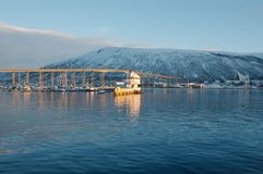 Harbor Bridge in Tromso, Norway. Tromsø harbour bridge and Arctic cathedral, with a snowy mountain in the background and blue sea in the foreground Royalty Free Stock Photography