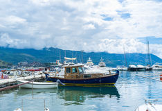 The harbor of Budva. BUDVA, MONTENEGRO - JULY 12, 2014: The shipyard with the old fishing boats, tiny tourist boats and luxury yachts surrounded by mountains Royalty Free Stock Images
