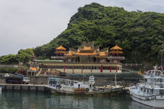 Harbor in the city Wanli next to Yehliu park with a temple in the backround Royalty Free Stock Photography