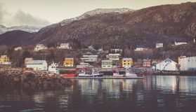 Harbor con le barche e gli yacht attraccati con i picchi innevati nei precedenti nel paesino di pescatori immagini stock