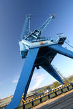 Harbor crane in blue sky. Port crane in Linz, Austria. Huge crane used to clear ships to boxcars at the Danube river. Although a still life, very dynamic picture Stock Photography
