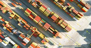 4K aerial view of harbor crane moving diagonally above colorful containers in the port