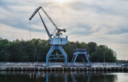 Harbor crane on the sunset sky Stock Image