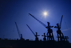 Harbor cranes no.1. Shapes of cranes at a cargo harbor in backlight Royalty Free Stock Photography