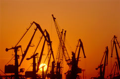 Harbor cranes at sundown Stock Photos
