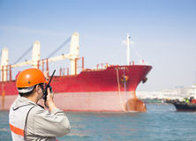 Harbor dock worker talking on  radio Stock Image