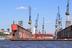 Harbor dry dock. Hamburg, Germany - port seen from river Elbe. Industrial harbor cranes and dry dock Stock Photo