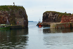 Harbor of Dunbar. Motor vessel entering the harbor of Dunbar in Scotland stock photo