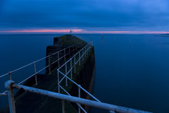 Harbor at dusk. Harbour wall and lighthouse in picturesque fishing village of Pittenweem, East Neuk, Fife, Scotland, UK, at dusk Royalty Free Stock Photo