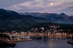 Harbor before dusk. Lighthouse, mountains, moon and boats Stock Photography