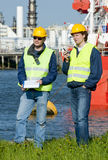 Harbor Engineers. Two harbor engineers with radios, personal safety equipment and a clip board Royalty Free Stock Image