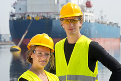 Harbor entrepreneurs. Male and female entrepreneurial engineers posing happily in front of a large industrial vessel Royalty Free Stock Photos