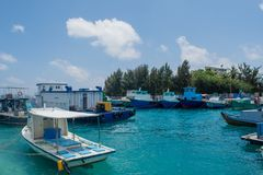 Harbor full of small fishermen`s and cargo boats located at the Villingili tropical island Royalty Free Stock Photography