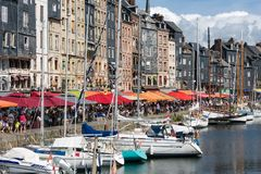 Harbor historic city Honfleur with moored sailing ships and restaurants Royalty Free Stock Images