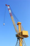 Harbor industrial crane. Yellow crane in harbor over blue sky Stock Photography