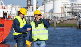 Harbor inspection. Two dockers during a routine inspection of an industrial harbor stock photography