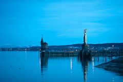Harbor lights at dusk. Lights and buildings at dusk along the shore at Constance Harbor, Lake Constance, Germany Stock Photo