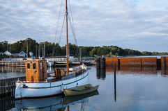 Harbor with little fisherboat. Harbor with little blue fisherboat with bright blue sky stock image