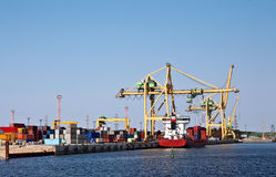 Harbor logistics. Loading of container ship with portal cranes royalty free stock photography