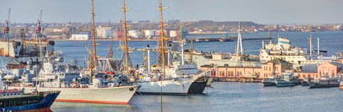Harbor with military and sailing ships. Three-masted sailing ship Friendship and a military cruiser in the port of Odessa at sunset stock photography