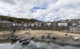 Harbor of Mousehole in Cornwall. Mousehole, England - April 28, 2017: Panorama of Mousehole with the harbor, houses and the tide, Cornwall Royalty Free Stock Photos