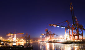 Harbor at night. Panorama image of an illuminated cargo port at night with container terminals, cargo ships and cranes and a clear blue sky. Ships and boats in Stock Image