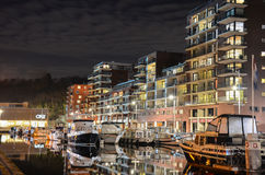 Harbor by night. An urban landscape in the port area. Behind the boats you see the recently built expensive lofts, part of a new housing project, developed by stock images