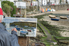 Harbor painter. An elderly painter is painting the boats in a harbor Stock Images