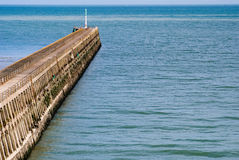 Harbor pier leading out to sea stock photos