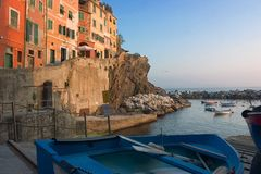 Harbor in Riomaggiore. Little harbor with boat at sunset in Riomaggiore - Cinque Terre - Italy Stock Image