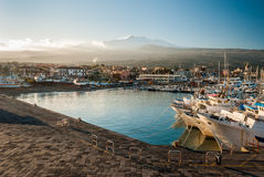 The harbor of Riposto during the sunset; snowy volcano Etna in the background Royalty Free Stock Image