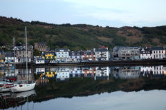 Harbor's Twilight Reflection. Reflected perfectly in the calm waters of a Scottish harbor, the isolated waterfront of the fishing village of Tarbert--with its Stock Photography