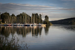 Harbor of sailboats on the shore of a Lipno Dam reflecting in water at sunset Stock Image
