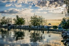 Calm lake, harbor and pier at sunrise. Harbor with sailing boats and pier at dawn with dramatic clouds reflected in water, Lake Balaton, Hungary Royalty Free Stock Images