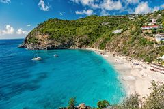 Harbor with sand beach, blue sea and mountain landscape in gustavia, st.barts. Summer vacation on tropical beach. Recreation, leisure and relax concept royalty free stock photography