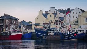 Harbor Scene In The Evening. Generic harborside scene with car driving past fishing boats stock footage
