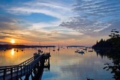Harbor at sunrise. A view of a peaceful Maine harbor and wharf as the first light of day reflects off the clouds and the quiet water. Southwest Harbor, Maine royalty free stock photos