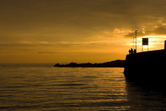 Harbor at sunset. Sunset silhouette at harbour in Elie, East Neuk, Fife, Scotland featuring people for scale Royalty Free Stock Photo
