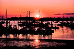 Harbor Sunset. The late summer sun paints a red glow across the sky and harbor as the sailboats rest for the evening royalty free stock photo