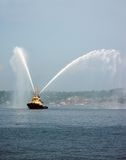 Harbor Tug Boat. A tug boat spraying its jets in Halifax Harbor Royalty Free Stock Image