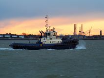 Harbor tug makes its way up the river back to port against an orange sunset. Harbor tug from the Port of Felixstowe makes its way up the river back to port Royalty Free Stock Photography