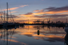 Harbor Twilight docked sailboats and cargo port cranes Royalty Free Stock Photo