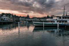 Harbor view from next to the train station in beautiful Luzern Lucerne Switzerland. A boat passes through half the frame royalty free stock images
