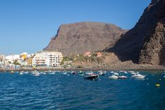 The Harbor of Vueltas in Valle Gran Rey with boats, buildings and mountains royalty free stock photography