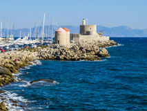 Harbor windmills and lighthouse. Rhodes, Greece Royalty Free Stock Photo