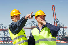 Harbor workers. Two dockers in discussion, in front of a large industrial harbor Royalty Free Stock Photo
