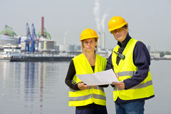 Harbor workers. Two harbor workers discussing plans and blueprints for a new construction site on location at an industrial harbor Royalty Free Stock Photos