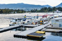 Harbour Air seaplanes/float planes/ pontoon planes docked in Coal Harbour, Vancouver, with Chevron Fueling Station in background stock photo