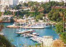 Harbour in Antalya, Turkey. View  on harbour in town Antalya, Turkey, boats onthewater, old and modern buildings on the banks, tropic vegetation Royalty Free Stock Images